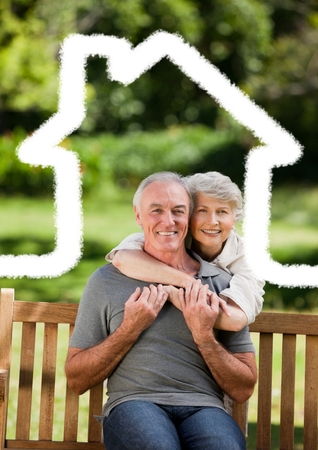Digital composite image of senior couple sitting in the park with home outline photo