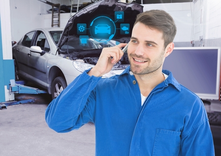 auto focus: Mechanic talking on mobile phone with car mechanic interface in garage