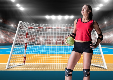 Digital composite image of female athlete holding handball against stadium in background