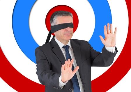manos unidas: Digital imagen conceptual compuesta del hombre de negocios con banda de color negro en los ojos contra la Junta de tiro con arco