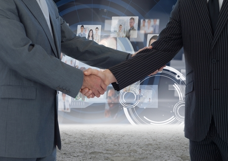 Digital composite image of business professionals shaking hands against technology background photo