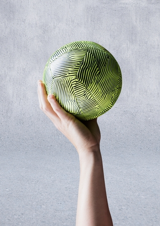 Digital composite image of athlete hand holding ball against concrete background