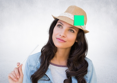 early twenties: Digital composite image of thoughtful female executive wearing hat with sticky note against white background Stock Photo
