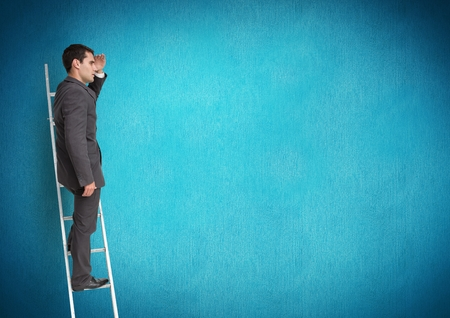 Businessman on ladder looking at a distance against blue background Stock Photo