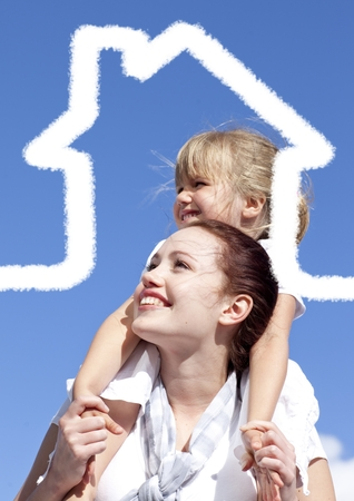 Happy mother carrying her daughter on shoulder on a sunny day with digitally generated house outline photo