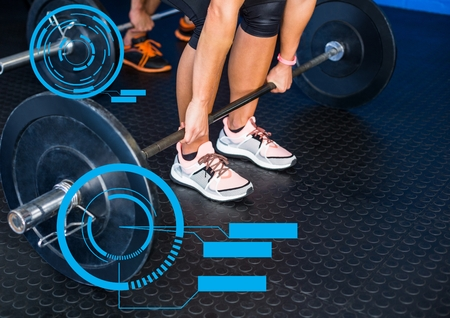 Digital composite image of fit man performing dead lift exercise in gym with fitness interface