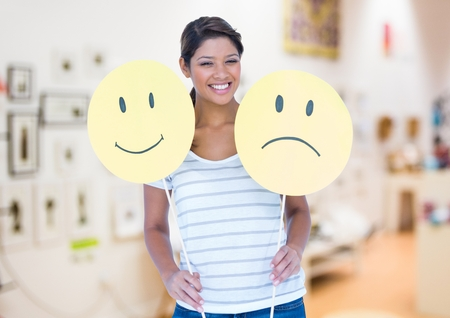 Smiling woman holding happy and sad smiley faces