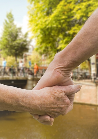 Close-up of senior couple holding hands against canal bridge in background Stock Photo