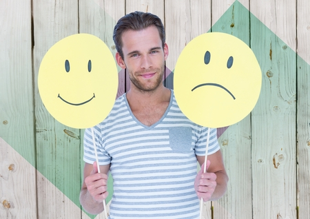 Man holding happy and sad smiley faces against wooden background Stock Photo
