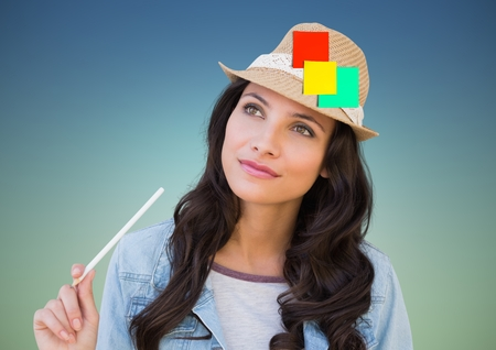 Woman holding pencil with sticky notes stuck on her hat against blue background Stock Photo