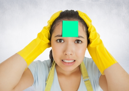 overwhelmed: Worried female cleaner with sticky note on her forehead against white background Stock Photo