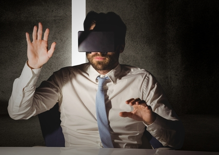 high def: Man pretending to touch while wearing virtual reality headset at desk