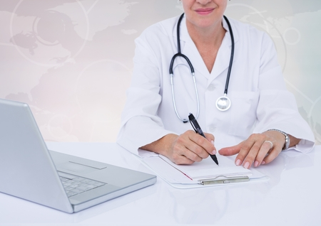 Digital composite image of doctor writing on clipboard on desk with digital world map in background Stock Photo