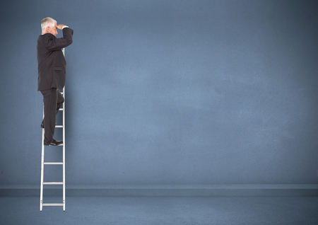 peering: Businessman on ladder looking at a distance against blue background Stock Photo