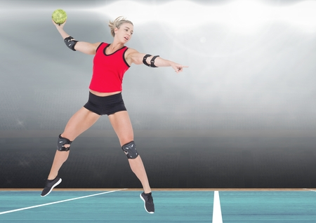 Player jumping while playing handball in stadium