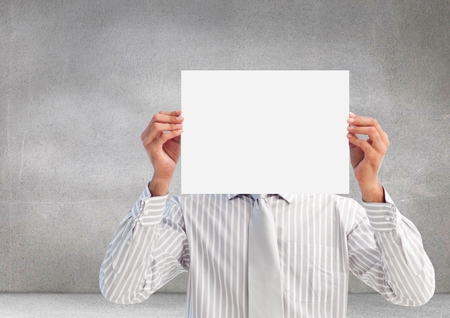 Digital composite image of male executive covering his face behind paper against grey background