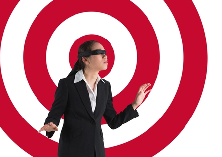 Digital composite conceptual image of businesswoman with black band on eyes against archery board