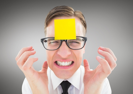 Frustrated man with sticky note on his forehead against grey background