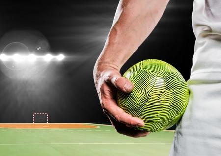 terrain de handball: Numérique image composite de l'athlète masculin tenant handball dans le stade