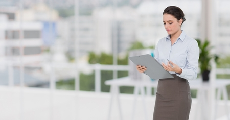 Concentrated businesswoman holding a clipboard at office