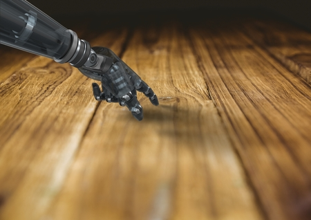 cropped: Digital composition of robot hand touching wooden desk