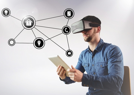 Digital composition of man using virtual reality headset and digital tablet and networking icons in background Stock Photo
