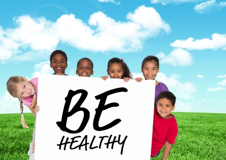 nightwear: Digital composition of kids holding card showing text  be healthy in front of blue sky and grass