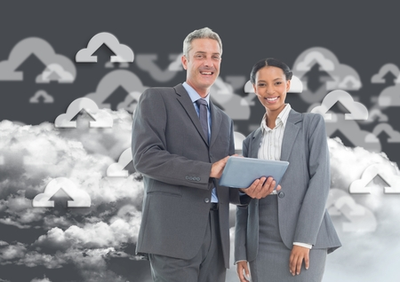 smolder: Happy businessman and businesswoman using digital tablet against digitally generated connecting icons