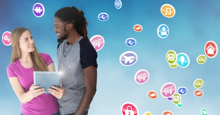 Smiling couple holding digital tablet against digitally generated icons background