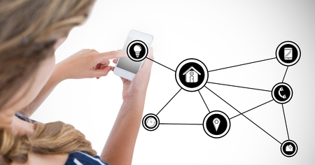Woman using smart phone with digitally generated icons against white background