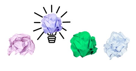 Digital composition of multi colored crumpled paper with bulb on white background Stock Photo