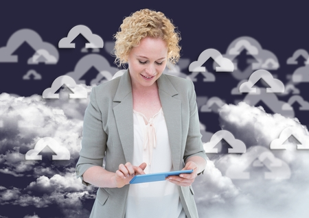 Woman using digital tablet against digitally generated cloud computing icons in  background