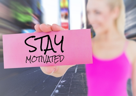 Composite image of woman holding placard that reads stay motivated against city in background Stock Photo
