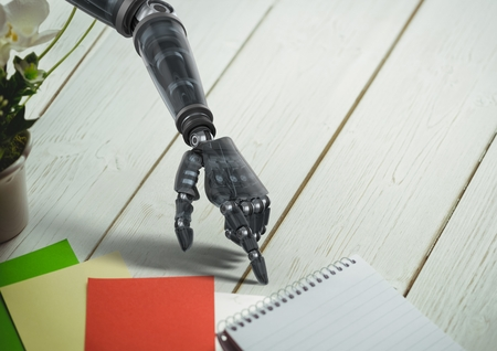 Close-up of robot hand pointing at spiral diary on wooden table