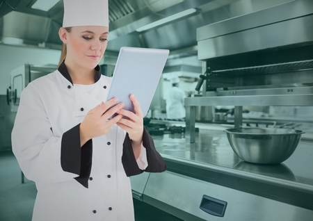 gas stove: Composite image of chef using digital tablet in commercial kitchen Stock Photo