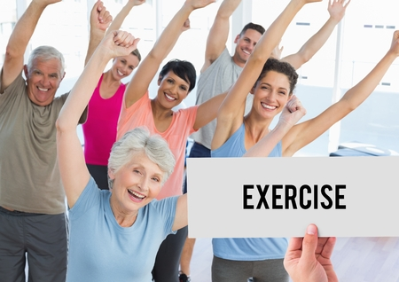 Hand holding placard that reads exercise against people doing aerobics in fitness studio photo