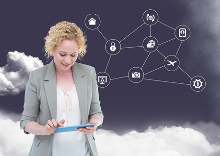 Digital composition of businesswoman using digital tablet with networking icons and cloud in background Stock Photo