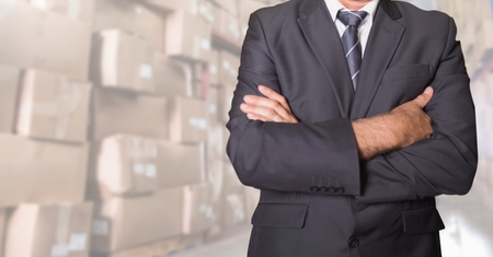 Mid section of businessman standing with his arms crossed at warehouse