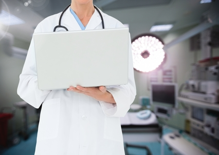 Mid section of doctor using laptop against operating room in background