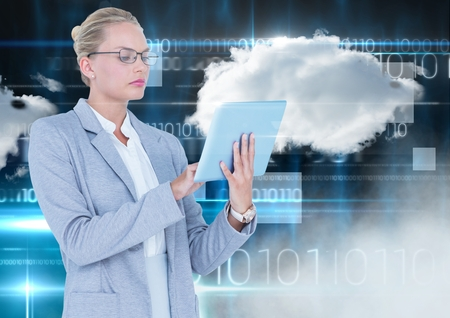 Digital composition of businesswoman using digital tablet with cloud and binary codes in background Stock Photo