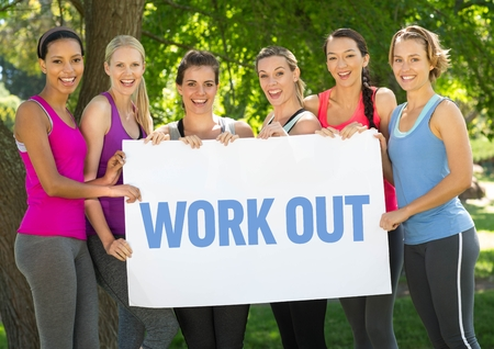 scrolling: Portrait of happy women holding placard with text workout in park