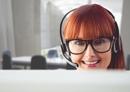 Portrait of a happy woman talking on headset in customer service office