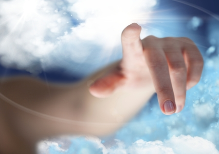 Close up of hand pointing against cloudy sky in background