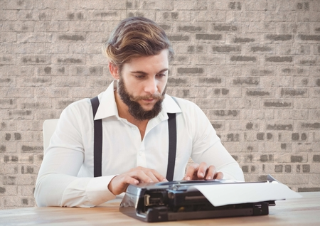 Retro style man using a typewriter at desk Stock Photo