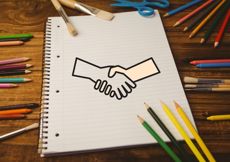 introducing: Digital composition of drawn handshake shape on notebook with color pencils on wooden table