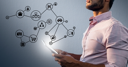 smart goals: Digital composition of man holding digital tablet with networking icons in background Stock Photo