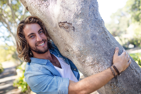 Portrait of smiling man hugging a tree trunk in park