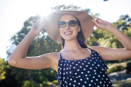 Happy woman wearing sunglasses and hat in park