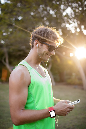 Happy man listening to music on mobile phone in park Stock Photo