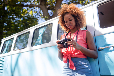 Woman leaning on campervan and checking photo on camera in park on a sunny day Stock Photo